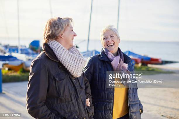 affectionate lesbian couple walking by sea - friendship stock pictures, royalty-free photos & images