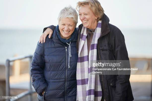 affectionate lesbian couple walking near sea - weekend activities stock pictures, royalty-free photos & images