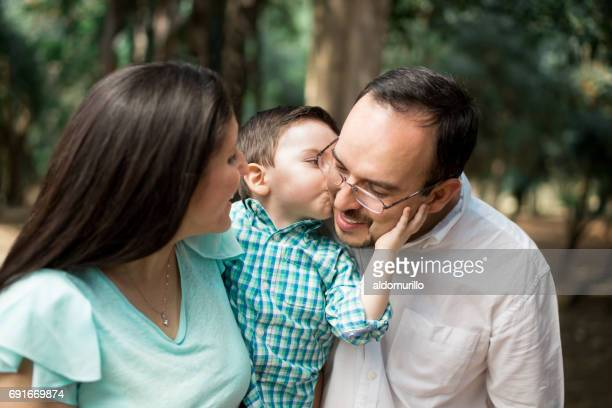 Affectionate little boy kissing father on cheek