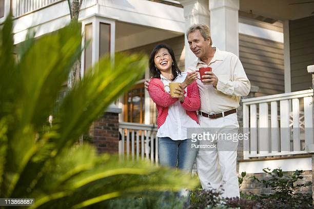 Affectionate mature couple holding coffee mugs in front of their house