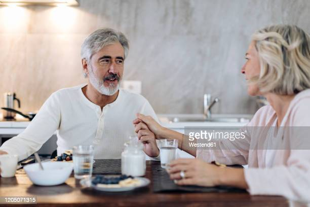 affectionate mature couple sitting at table in kitchen at home having breakfast - heterosexual couple stock pictures, royalty-free photos & images