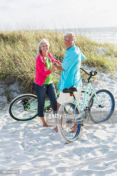 Zärtlich Älteres Paar mit Fahrrädern am Strand