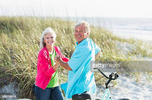 Affectionate mature couple with bikes at beach
