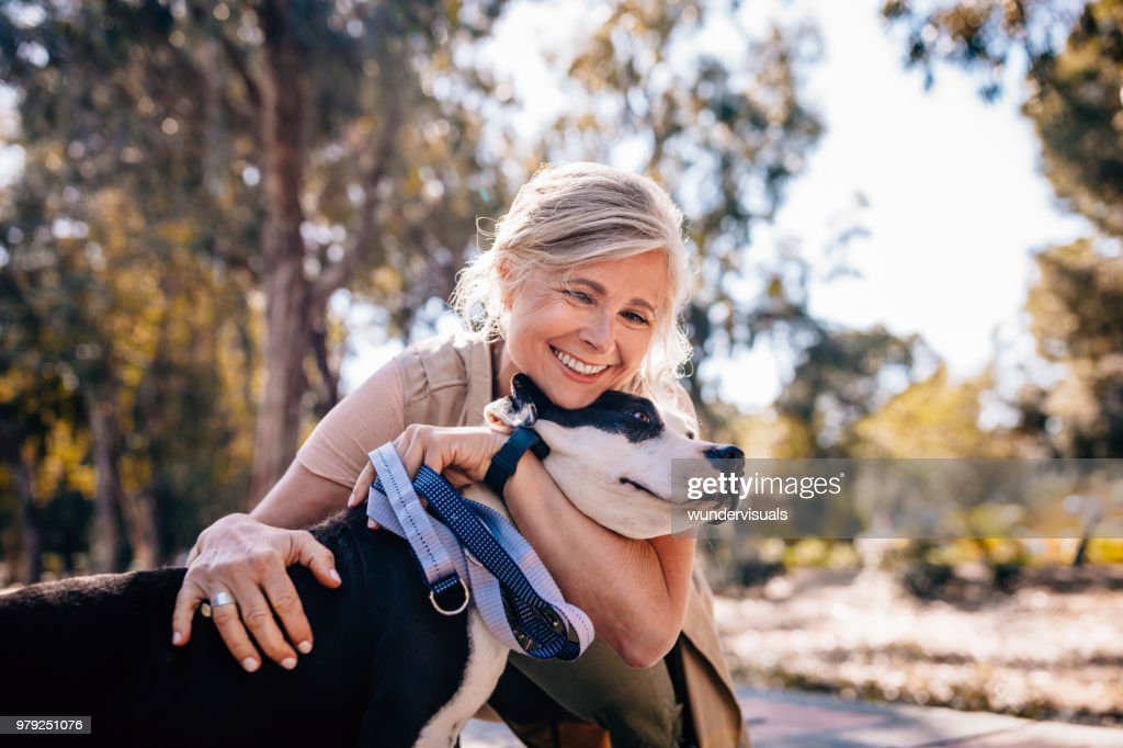Affectionate mature woman embracing pet dog in nature : Stock Photo