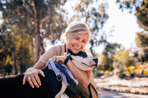 Affectionate mature woman embracing pet dog in nature 979251076