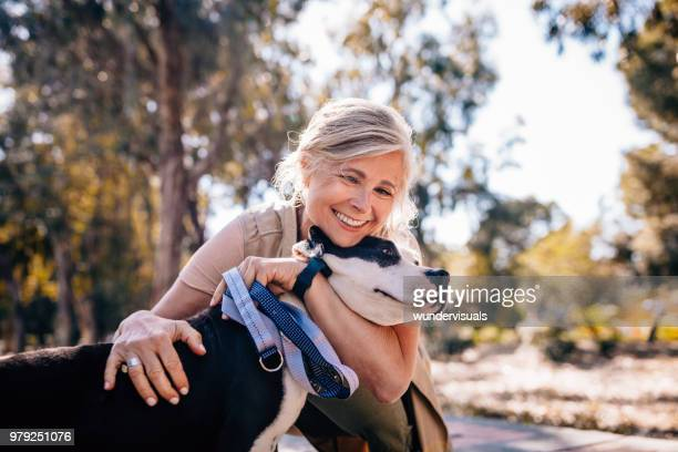 affectionate mature woman embracing pet dog in nature - mulheres maduras imagens e fotografias de stock