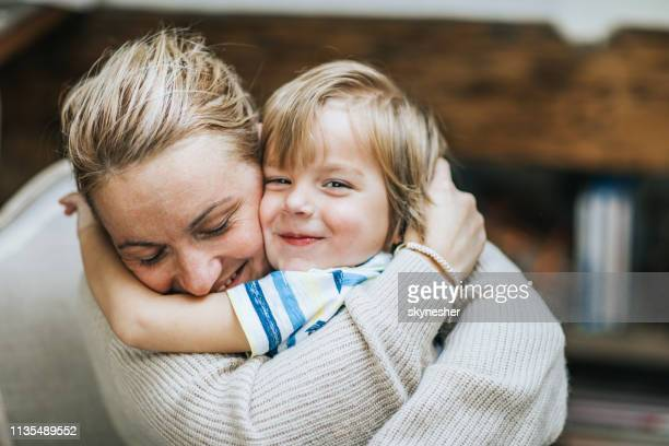 affectionate mother and son embracing at home. - offspring stock pictures, royalty-free photos & images