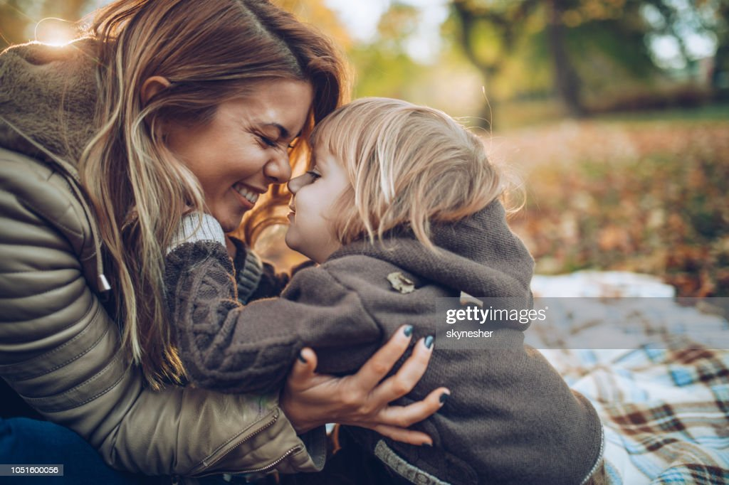Affectionate mother and son having fun while rubbing their noses in nature. : Stock Photo