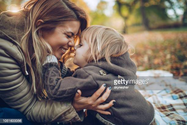 affectionate mother and son having fun while rubbing their noses in nature. - mother stock pictures, royalty-free photos & images