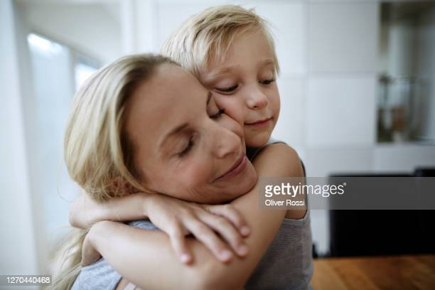 affectionate mother and son with closed eyes hugging at home - embracing fotografías e imágenes de stock