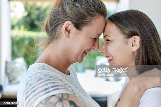 affectionate mother and teenage daughter hugging and touching foreheads - forehead stock pictures, royalty-free photos & images