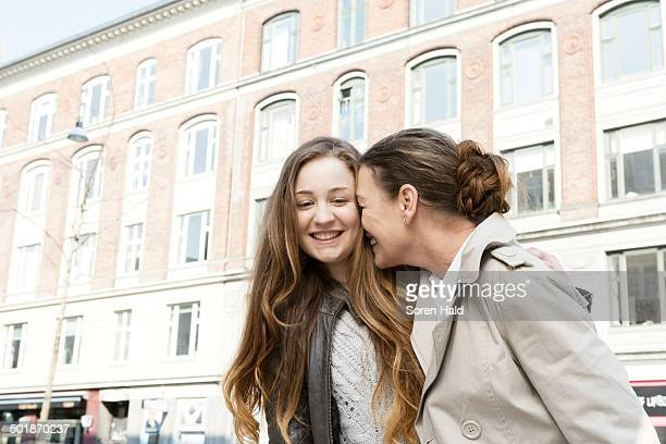 Affectionate mother and teenage daughter on city street