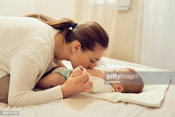Affectionate mother in bedroom kissing baby's belly.