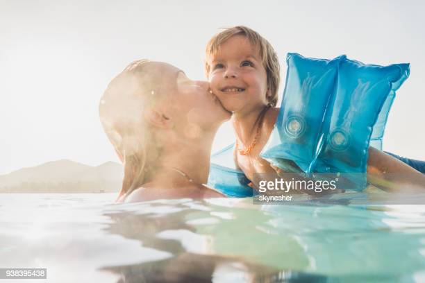 affectionate mother kissing her small son in the sea. - armband stock pictures, royalty-free photos & images