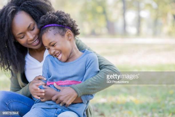 Liebevolle Mutter neckt junge Tochter außerhalb