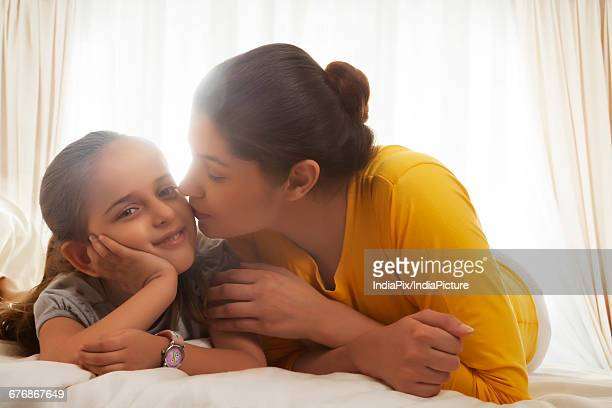 affectionate mother with daughter in bed - indian girl kissing stock photos and pictures