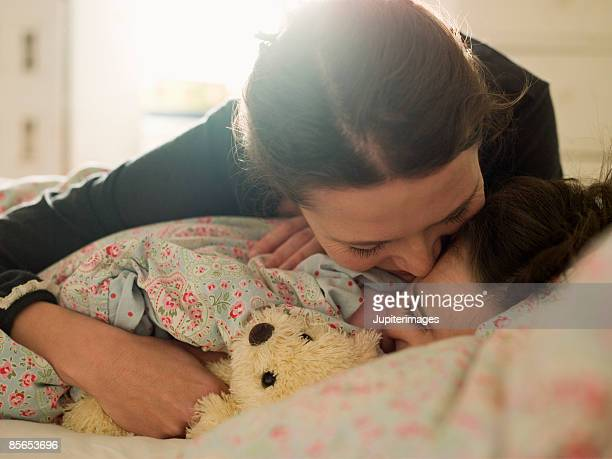 affectionate mother with daughter in bed - good morning kiss images stock photos and pictures