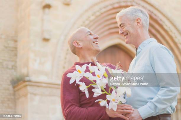 affectionate older gay male couple with bouquet of flowers outside church - civil partnership stock pictures, royalty-free photos & images