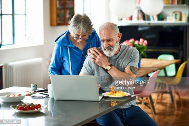 affectionate retired couple with laptop in kitchen - finance and economy stock pictures, royalty-free photos & images