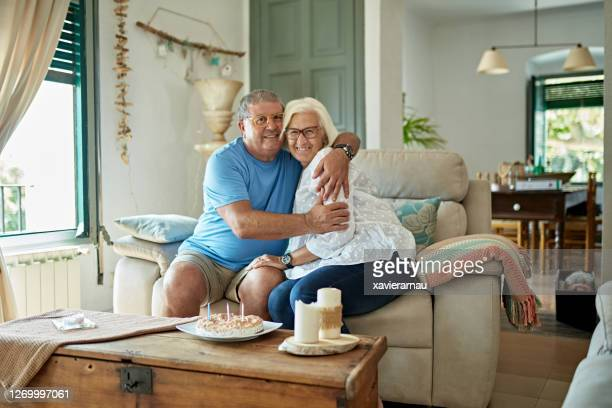 affectionate senior couple celebrating their anniversary at home - two seater sofa stock pictures, royalty-free photos & images