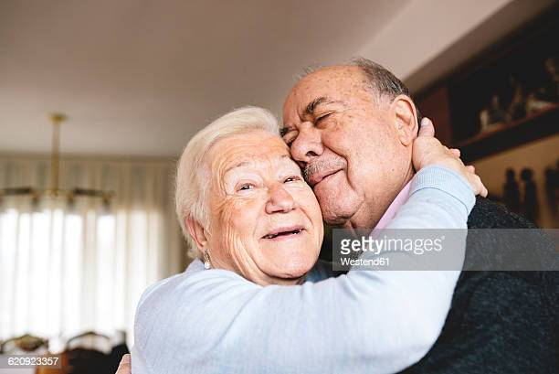 Affectionate senior couple hugging at home