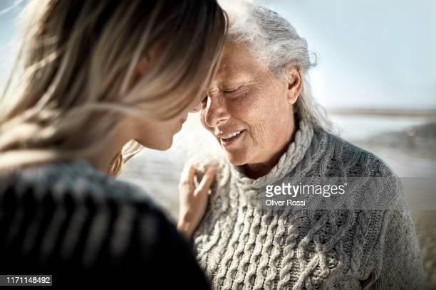 affectionate senior woman with her adult daughter on the beach - verhalten und emotionen stock-fotos und bilder
