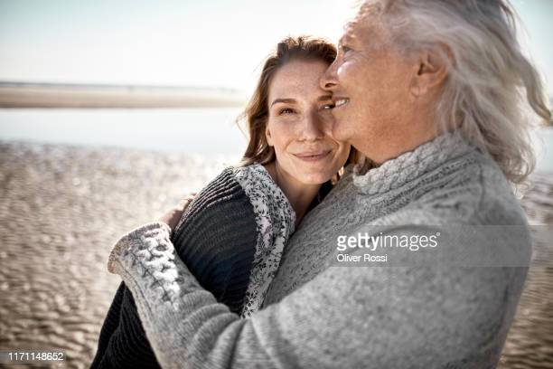affectionate senior woman with her adult daughter on the beach - schleswig holstein stock pictures, royalty-free photos & images