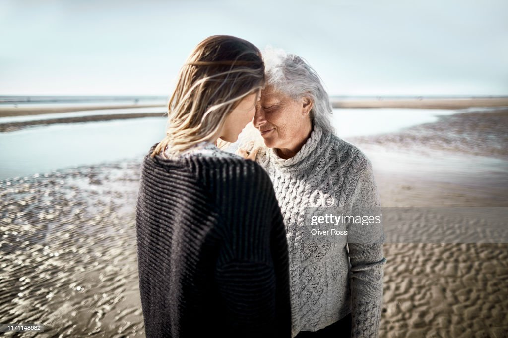 Affectionate senior woman with her adult daughter on the beach : Stock Photo