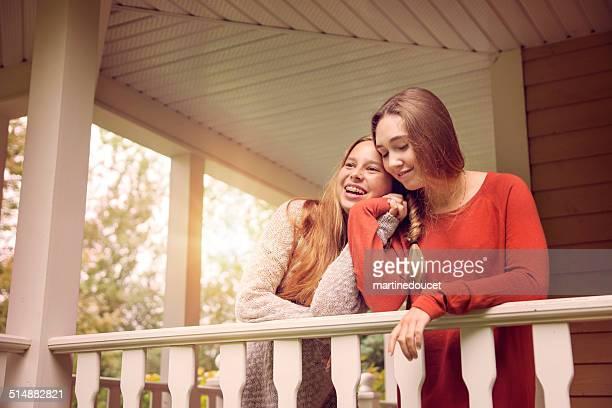 Affectionate teenage girlfriends hugging on a house veranda in autumn.