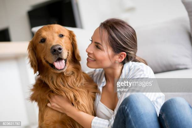 Femme affectueuse, caressant son chien à la maison