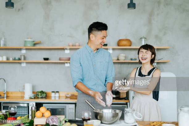 affectionate young asian couple having fun while baking together in a domestic kitchen - baking bread stock pictures, royalty-free photos & images