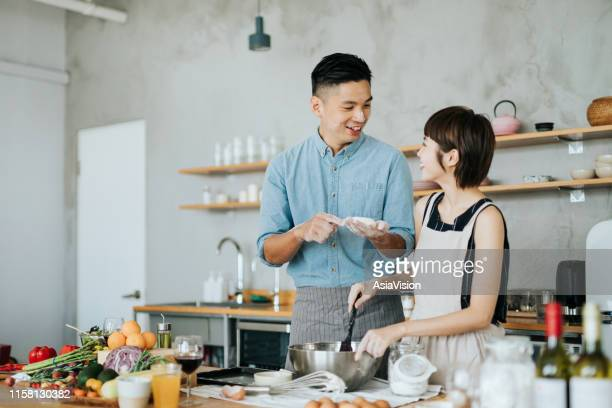 affectionate young asian couple preparing cookies together in a domestic kitchen - domestic life imagens e fotografias de stock