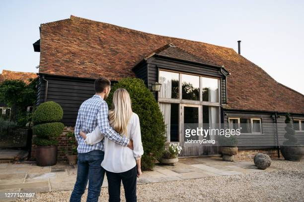 affectionate young couple admiring home in west sussex - outdoors stock pictures, royalty-free photos & images