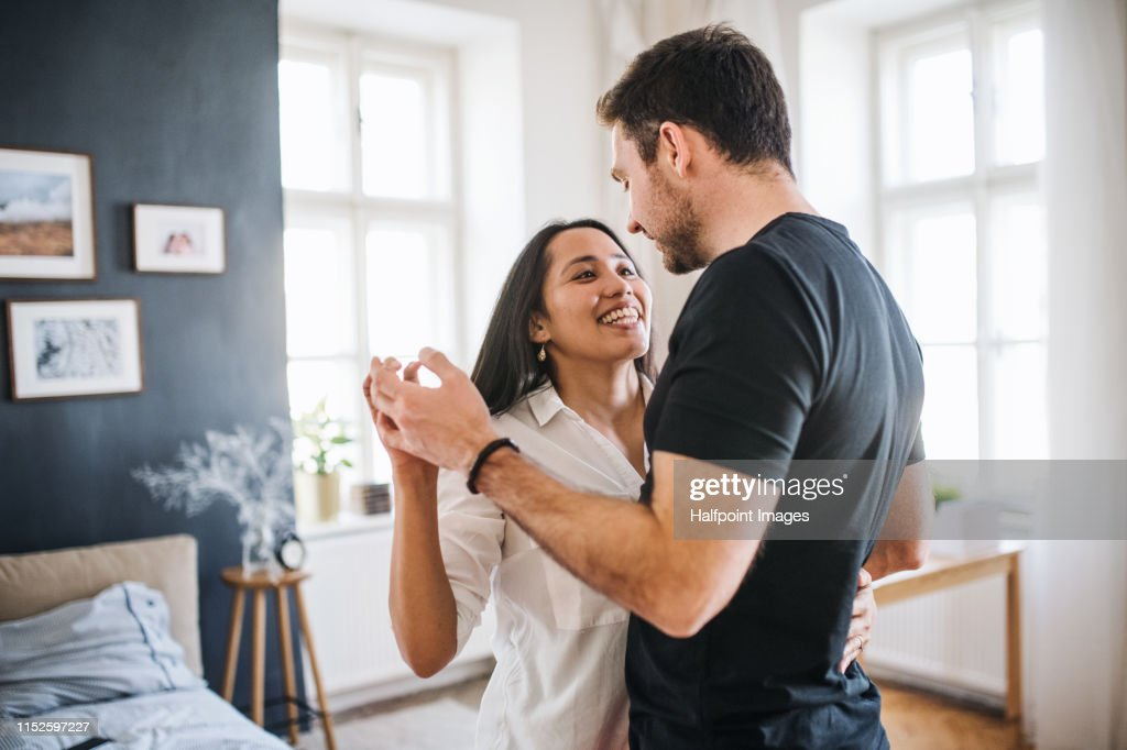Affectionate young couple in love dancing at home, having fun. : Stock-Foto