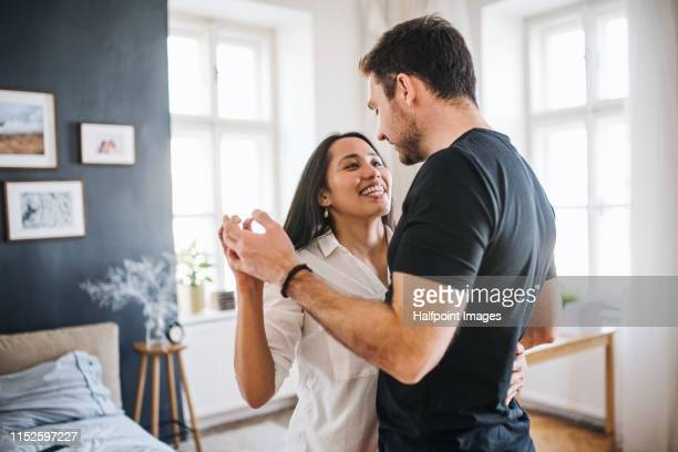 affectionate young couple in love dancing at home, having fun. - koppel stockfoto's en -beelden