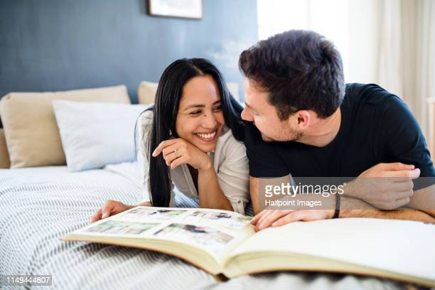affectionate young couple in love lying on bed at home, looking at photographs. - beautiful wife pics stock pictures, royalty-free photos & images