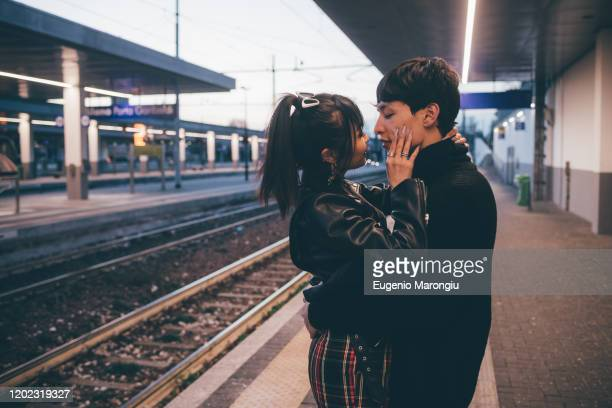 affectionate young couple on train station platform, milan, italy - teenage couple stock pictures, royalty-free photos & images