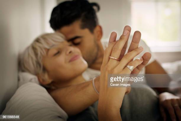 affectionate young man kissing woman while holding hand in bedroom - couple lit photos et images de collection