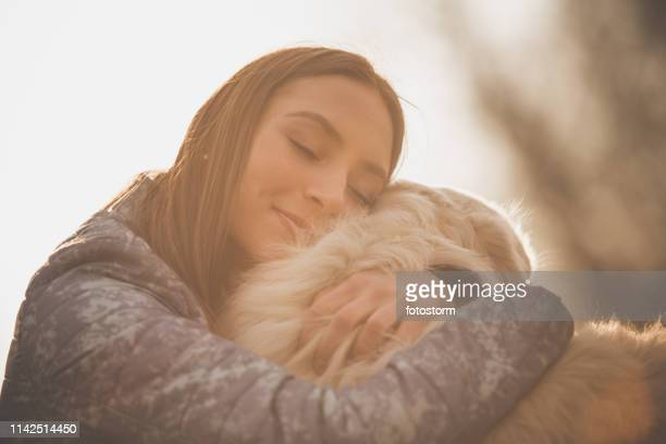 affectionate young woman hugging her dog - human head stock pictures, royalty-free photos & images