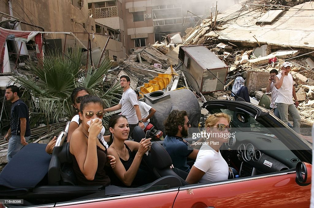 Affluent Lebanese drive down the street to look at a destroyed neighborhood August 15, 2006 in southern Beirut, Lebanon. As the United Nations brokered cease fire between Israel and Hezbollah enters its first day, thousands of Lebanese returned to their homes and villages.