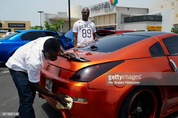 Affluent men meet and show off their fancy sport cars at a shopping mall parking on April 19 2015 in Accra Ghana Many young unemployed men here are...