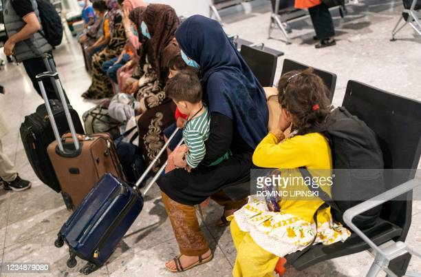 Afgan refugees wait to be processed after arriving on an evacuation flight from Afghanistan, at Heathrow Airport, London on August 26, 2021. - A...