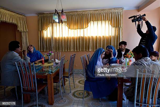 """Afghan actress Trena Amiri laughs with actor Ghafar Zalam at a restaurant as an Afghan familiy eats lunch, during the filming of the soap opera """"Love..."""