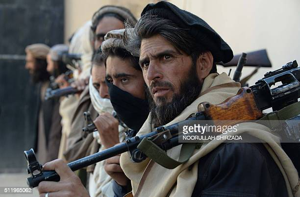 Afghan alleged former Taliban fighters carry their weapons before handing them over as part of a government peace and reconciliation process at a...