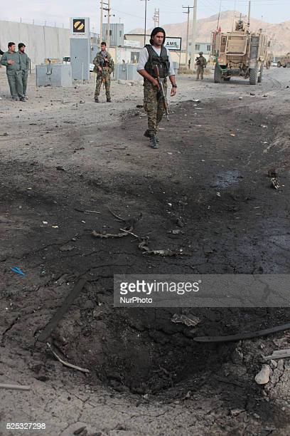 Afghan and foreign security forces investigate the site of a suicide attack targeting an ISAF convey near a military camp in the outskirt of Kabul,...