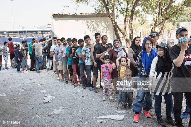 Afghan and Syrian refugees wait in line to be registered at the port of Mytilene on July 30 on the island of Lesvos Greece