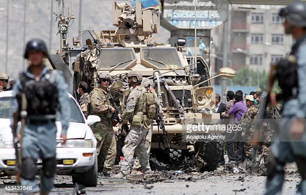 Afghan and US security forces inspect the wreckage of an armoured vehicle at the site of a suicide attack in Kabul Afghanistan on August 10 2014 An...
