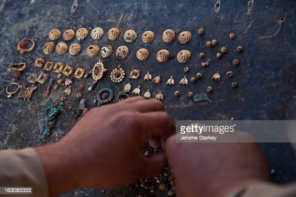 Afghan archeologists with a freshly discovered hoard of gold and jewels at Mes Ainak, south of Kabul, Nov 14, 2011. More than 250 labourers were...