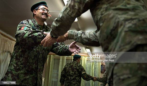 Afghan Army Colonel Abdul Sami Badakshani greets US Army Colonel Kimo C Gallahue Commander 4th Infantry Brigade Combat Team during a joint meeting on...
