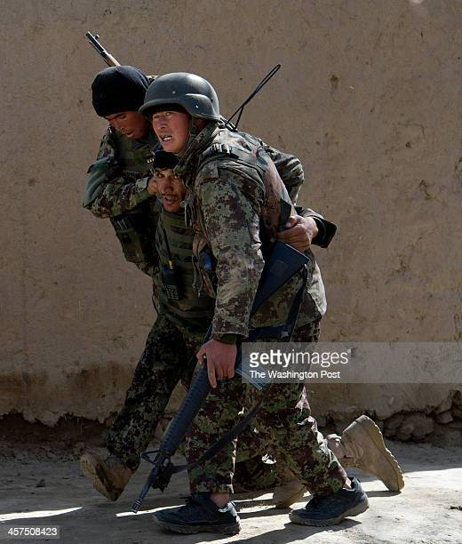Afghan Army soldiers carry their comrade after he was shot during a firefight while on an operation attempting to remove the Taliban from the area on...